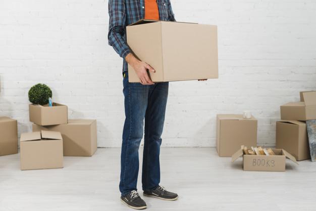 homme tenant un carton de déménagement dans les mains